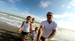 Young Caucasian father filming family self portrait enjoying Fall beach vacation Stock Footage