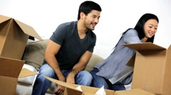 Stock Video Footage of Ethnic Couple Sitting White Couch New Home Unpacking