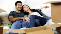 Young Ethnic Couple Taking Break Unpacking Moving Cartons Stock Footage