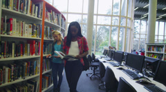Diverse student group working and studying together in college library. Stock Footage