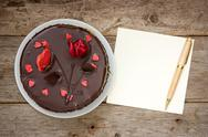 Stock Photo of chocolate cake with note paper and pen