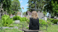 Girl sit near soldier boyfriend grave. Lithuania national flag Stock Footage