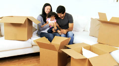Young Ethnic Family New Home Playing Moving Cartons - stock footage