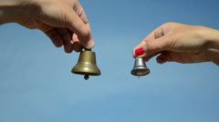 Boy and girl hands ding with silver bronze bell on blue sky Stock Footage