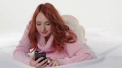 Redhead girl emotionally on the phone sms writes Stock Footage