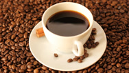 Stock Video Footage of Rotating white cup of coffee with coffee beans and cinnamon