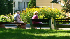 Elderly people sitting on benches. Summer. Stock Footage