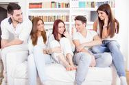 Stock Photo of friends having conversation on sofa at home