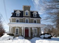 Greek revival house covered with snow - stock photo