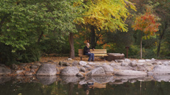 Pregnant Woman Sitting on Park Bench Stock Footage
