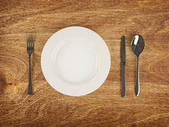 plate and flatware on wooden table - stock illustration
