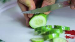 Chopping a green cucumber Stock Footage