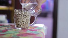 Adding water to chickpeas on a mug Stock Footage