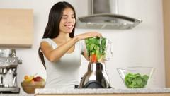 Woman making green vegetable smoothie Stock Footage