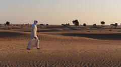 Arab man in the desert at sunset Stock Photos