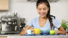 Woman eating breakfast cereals drinking juice Stock Footage