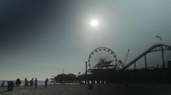Santa Monica Pier with fun-fair & flaring sun Stock Footage