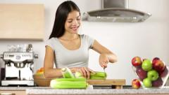 Woman cutting vegetables making food in kitchen Stock Footage
