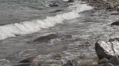 Waves slash rocky shore Slow Motion Stock Footage