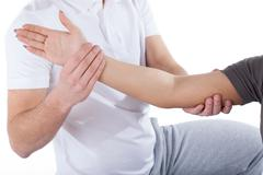 Physiotherapy doctor examining woman's elbow Stock Photos