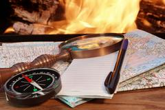 Road maps, compass,  notebook, pen and a magnifying glass Stock Photos