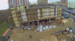 Builders work on facing of new shopping center building Stock Footage