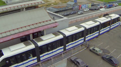 Electric train rides by monorail railway near road Stock Footage