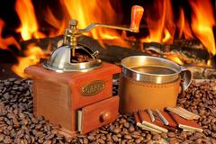 hot mug of coffee by the fire - stock photo