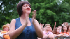 A smiling woman in blue blouse applauding at outdoor concert - stock footage