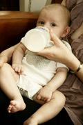 Infant drinking from baby bottle Stock Photos