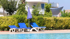 Empty blue lounger and umbrella near the hotels pool Stock Footage