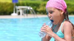 Little girl in a kerchief drink water from the bottle near pool - stock footage