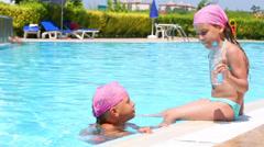 Two little girl near pool, one drink water from bottle. - stock footage