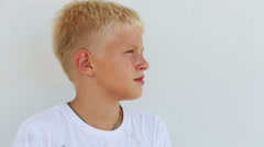 Young boy with blond hair stay close up near the wall Stock Footage