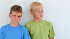 Two boys in colored T-shirt squint near the white wall Stock Footage