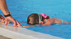 Adult man helps little girl learning to swim in pool Stock Footage