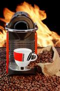 coffee machine with cup  of espresso near fireplace - stock photo