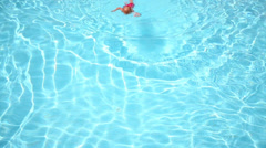 Little boy in red trunks swim in blue pool with clear water Stock Footage