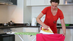 Beautiful housewife ironing laundry in the kitchen Stock Footage