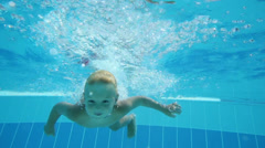 Cute little boy dives in blue hotels pool with open eyes Stock Footage