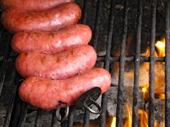 grilled sausages on grill, with smoke above it - stock photo