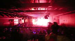 Crowd of people in large hall front of illuminated scene Stock Footage