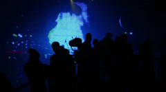 Silhouettes of people in front of scene in nightclub Stock Footage