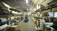 Large storage area with cardboard boxes stacked in a pile - stock footage