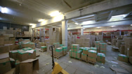 Stock Video Footage of Large storage area with cardboard boxes and loader