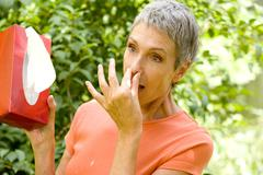 elderly person sneezing - stock photo
