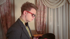 Two man retro style dressed in a room, one looking on records. Stock Footage