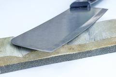 sharping stone with a kitchen axe - stock photo
