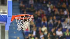 Ball fly into the basket at basketball court against spectators Stock Footage