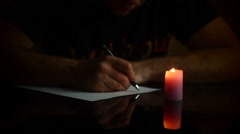 Man writes by candlelight Stock Footage